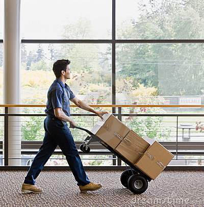 Free Side View Of Delivery Man Ipushing Stack Of Boxes Stock Image - 6604831