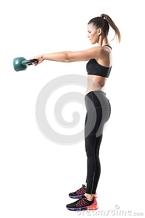 Free Side View Of Strong Sporty Fitness Woman Swinging 12 Kg Kettlebell In Mid Air Motion Stock Photos - 97915043
