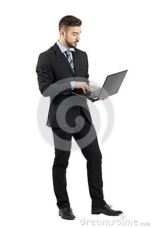 Free Side View Of Young Businessman In Suit Using Laptop. Stock Photography - 61952922