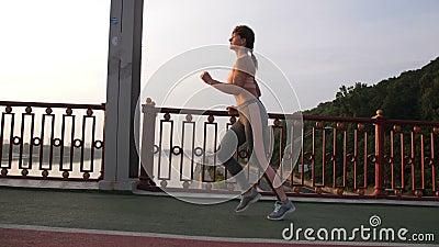 Side view of senior woman jogging across bridge. Side view of attractive redhead senior woman with fit body jogging in city across pedestrian bridge in the stock video