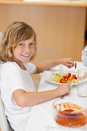 Side view of smiling boy at the dinner table