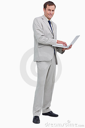 Side view of smiling businessman using his laptop