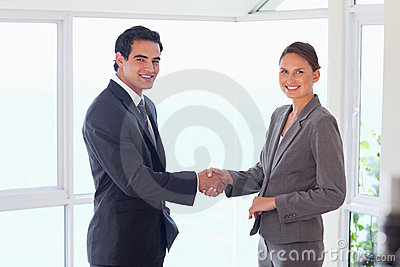 Side view of smiling trade partner shaking hands