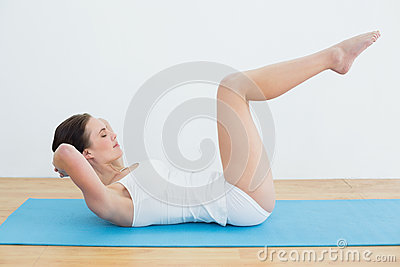 Side view of a woman doing stomach crunches on exercise mat