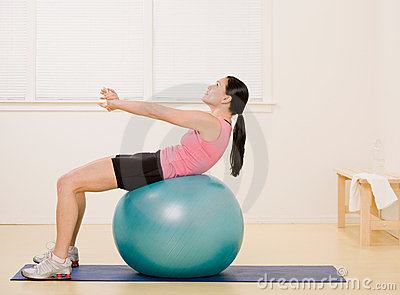 Side view of woman working out on exercise ball
