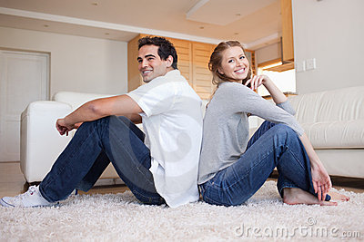 Side view of young couple sitting on the floor back-to-back