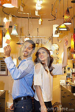 Side view of young couple standing back to back in lights store