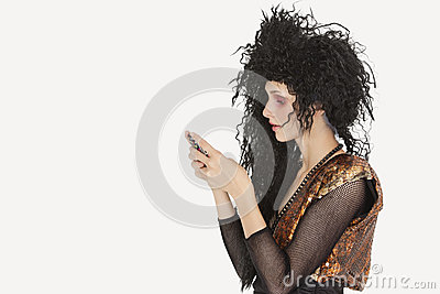 Side view of young Goth woman with teased hair texting on mobile phone over gray background