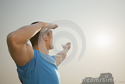 Side view of young muscular man stretching, hands raised towards the sky in Beijing, China