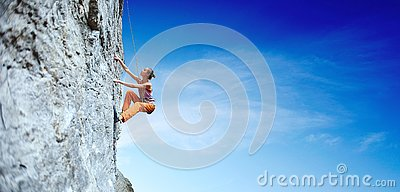 Young slim woman rock climber climbing on the cliff Stock Photo