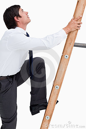 Side view of young tradesman climbing a ladder