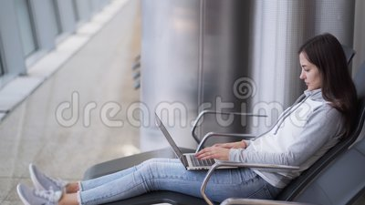 Young woman sits at departure lounge and uses laptop for work at airport. Side view of young woman sits at departure lounge and uses laptop for work at airport stock footage