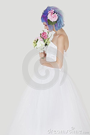 Side view of young woman in wedding dress with dyed hair against gray background