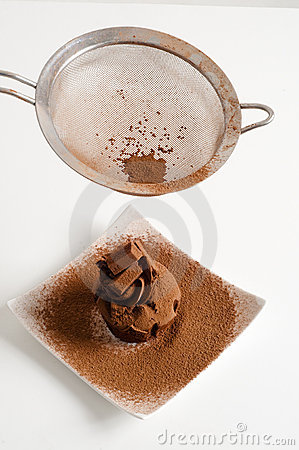 Sieving coco powder onto Chocolate muffin