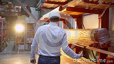 Siga a metragem do coordenador masculino do trabalhador do armazém dos empregados no funcionamento do capacete de segurança passe video estoque