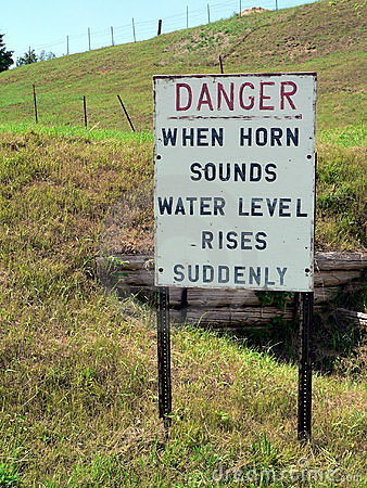 A sign indicates danger on a hill - When Horn Sounds Water Level Rises Suddenly