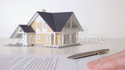 Sign mortgage contract. Mortgage contract (or insurance contract) sign. Man confirming mortgage contract and model of the house in background stock footage