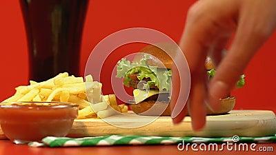 Signora che prende hamburger da pasto rapido combinato, patate fritte con salsa sul piatto di legno archivi video
