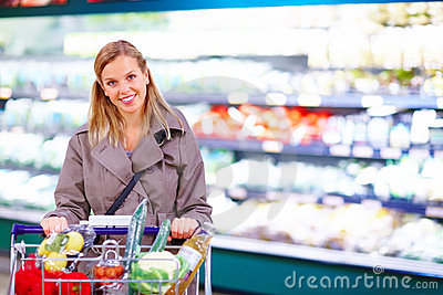 Signora che spinge un carrello di acquisto in un supermercato