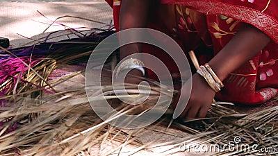 Signora del Bangladesh che porta il vestito tradizionale tesse la corteccia di bambù producendo la stuoia di bambù in Tangail, Ba stock footage