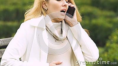 Signora incinta che soffre in pancia, chiamante 911, timore della consegna prematura stock footage
