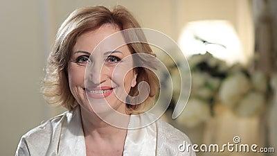 Signora senior affascinante che sorride e che esamina macchina fotografica video d archivio
