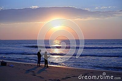 Sihoulettes surf fishing at sunrise