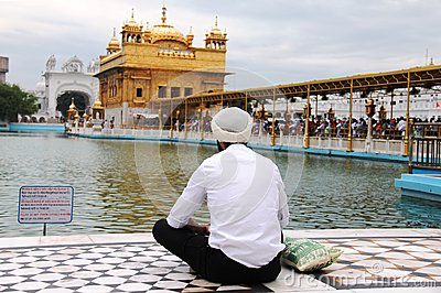 A Sikh guy praying in front of golden temple Editorial Stock Photo
