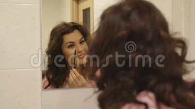 Sikten av den attraktiva brunetten målar hennes ögonfrans stock video