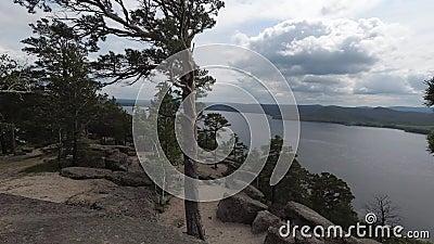 Sikten av den steniga sjön från berget med vaggar och träd från molnigt till soligt lager videofilmer