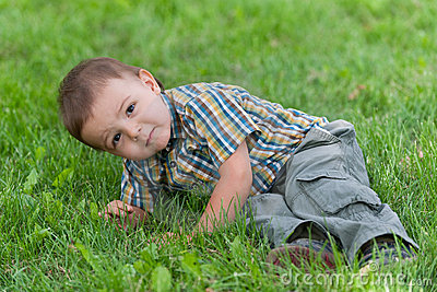 Silent strike of a toddler against the green grass