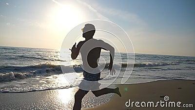 Silhouet van de jonge sportieve mens die snel langs kust tijdens zonsopgang lopen Atletische jongen opleiding op overzees strand  stock video