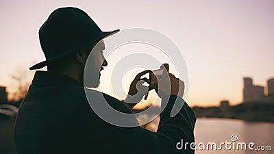 Silhouet van de reizigersmens in hoed die panoramische foto van de stadshorizon nemen op zijn smartphonecamera bij zonsondergang stock footage