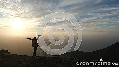 Silhouet van een meisje in fietshelm met rugzak die beelden van een ongelooflijke zonsondergang op de bovenkant van een Berg neme stock videobeelden