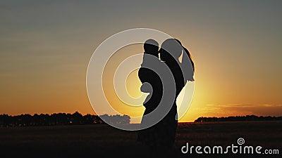 Silhouet van moeder met baby bij zonsondergang stock footage