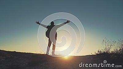 Silhouet van persoon in berg Jonge mens met rugzak die zich met opgeheven handen bovenop een berg bevinden Sport en stock videobeelden