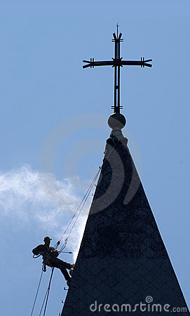 Silhouette of the alpinist cleans church roof