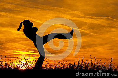 Silhouette of beautiful kick boxing girl exercising kick in the nature