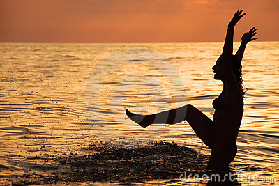 Silhouette beautiful woman play in sea in evening