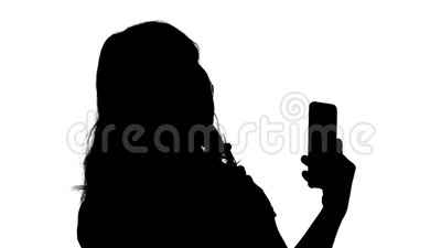 Silhouette Beautiful woman preen using her phone like a mirror. Close up. Side view. Silhouette Beautiful woman preen using her phone like a mirror stock footage