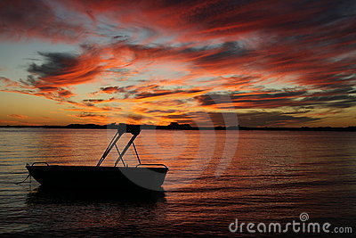 Silhouette of a boat in water sunset