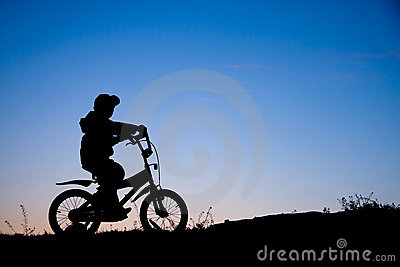 Silhouette of boy on bike