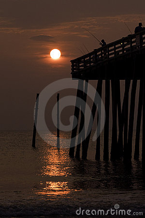 Silhouette of a boy fishing from a pier at sunrise