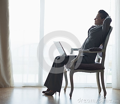 Silhouette of business woman sitting with laptop