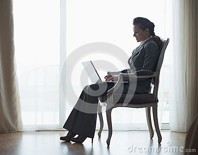 Silhouette of business woman working on laptop
