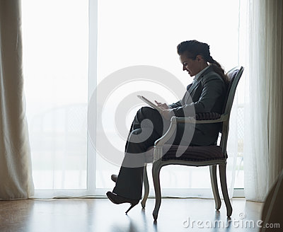 Silhouette of business woman working on tablet pc