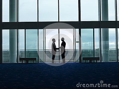 Silhouette Businessmen Shaking Hands At Airport