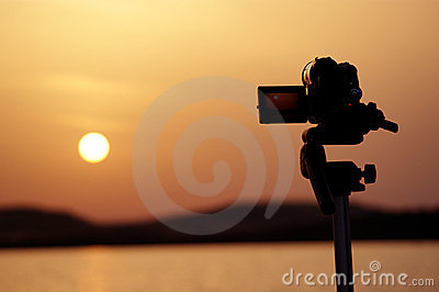 Silhouette of a camera taking videos of a sunset
