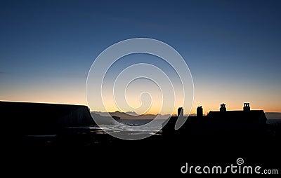 Silhouette of coastguard cottages at Seaford Head at sunrise