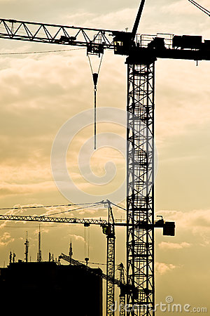 Construction cranes at sundown